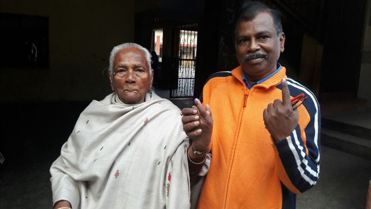 कानपुर में मतदान के बाद बूथ से बाहर आती 84 साल की बुजुर्ग महिला