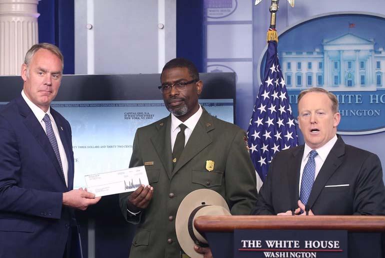 चेक सौंपते हुए व्हाइट हाउस के अधिकारी