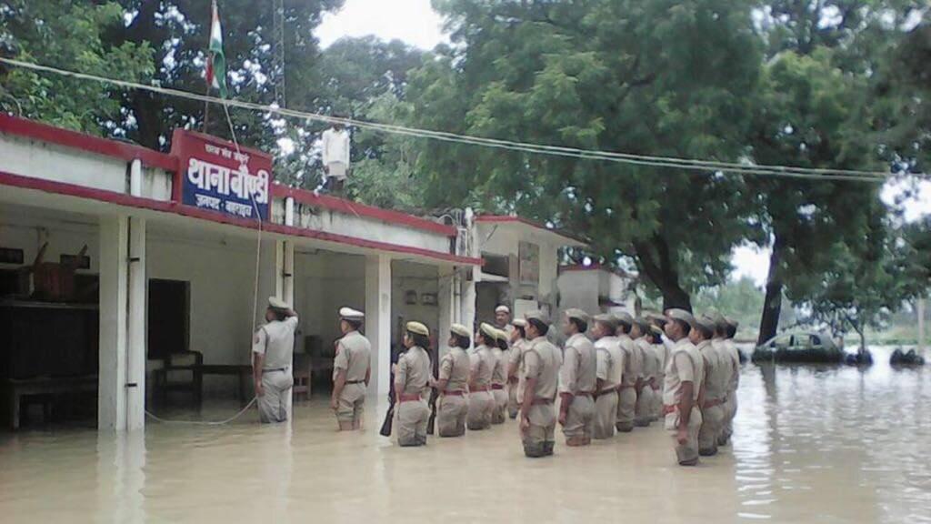 बाढ़ के पानी में खड़े होकर ध्वजारोहण करते पुलिसकर्मी