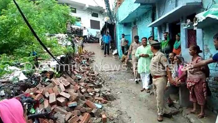 दीवार गिरने के बाद घटनास्थल पर खड़े लोग और मौके का मुआयना करती पुलिस