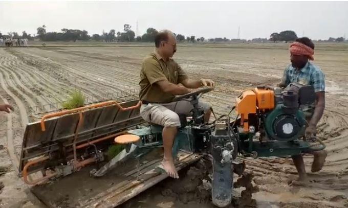 खेत में धान रोपाई मशीन का प्रदर्शन करते कृषि अधिकारी
