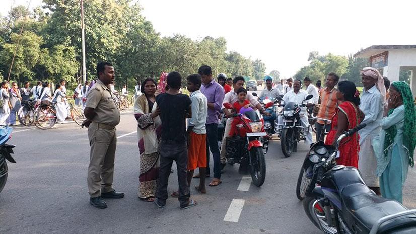 बच्चों के साथ गोरखपुर-सौनौली राष्ट्रीय राजमार्ग पर प्रदर्शन करती महिला