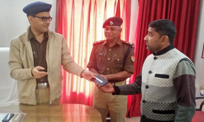 एसपी रोहित सिंह सजवान मोबाइल मालिकों को फोन देते हुए
