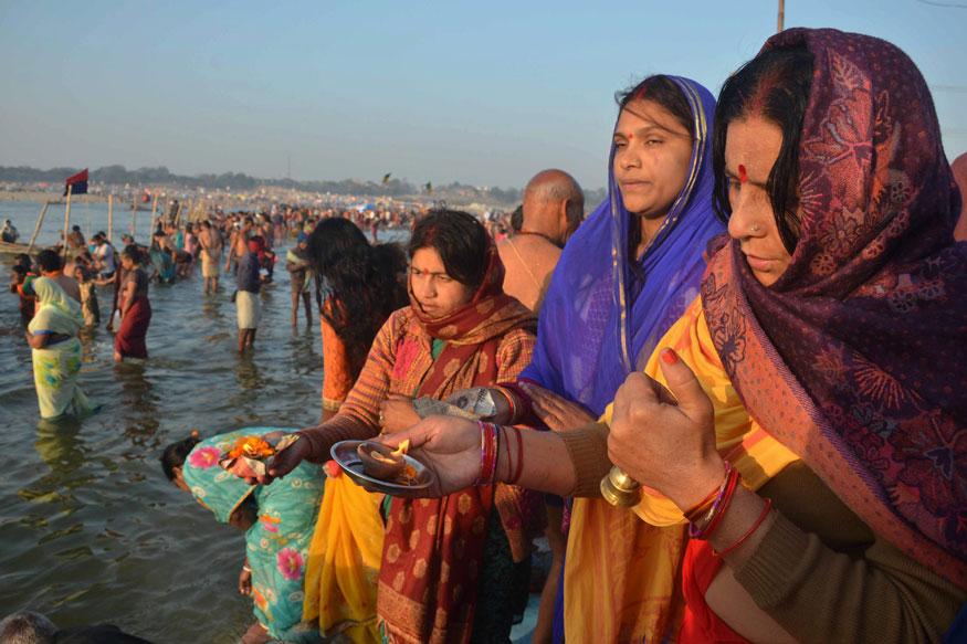 माघी पूर्णिमा पर डूबकी लगाने के बाद पूजा करती महिलाएं