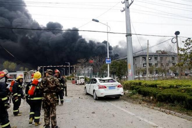 विस्फोट के बाद टूटी कार और उठता धुंआ