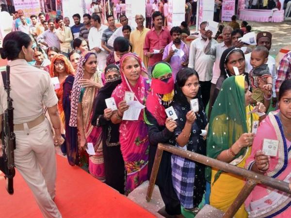 मतदान के लिए लाइन में लगे मतदाता और सुरक्षा करती महिला पुलिसकर्मी