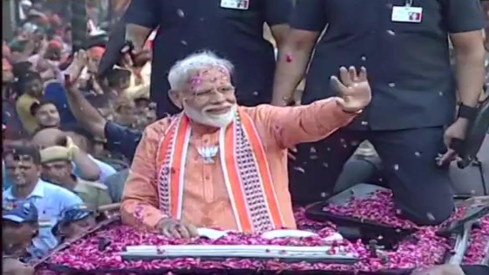 रोड शो में हाथ हिलाकर लोगों का अभिवादन करते प्रधानमंत्री मोदी