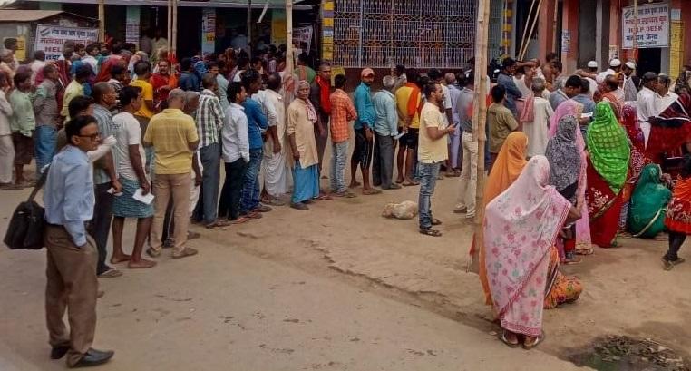वोट डालने के लिए लाइनों में खड़े मतदाता।