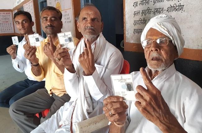 मतदान करने के लिए बैठे बुजुर्ग मतदाता