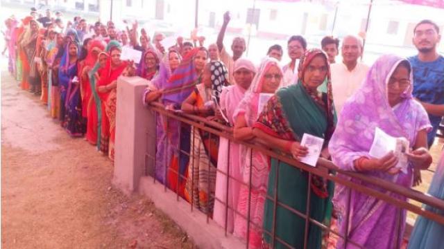 मऊ में मतदाान स्थल पर वोटिंग के लिए लाइन में खड़ी महिलाएं