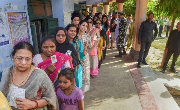 उत्तर प्रदेश के बूथ पर मतदान के लिए लाइन में खड़े उत्साहित मतदाता