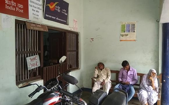 पोस्ट ऑफिस के बाहर सर्वर ठीक होने के इंतजार में बैठे लोग