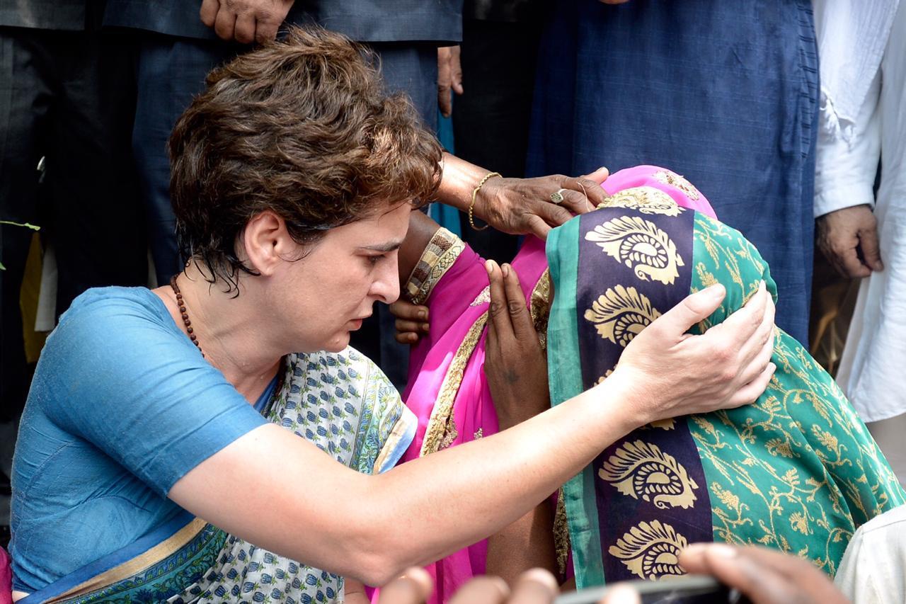 पीड़ित परिवार की महिला के आंसू पोंछती प्रियंका गांधी