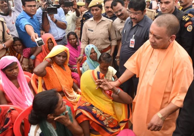 सोनभद्र के उम्भा गांव में पीड़ितों से मिलते सीएम योगी आदित्यनाथ