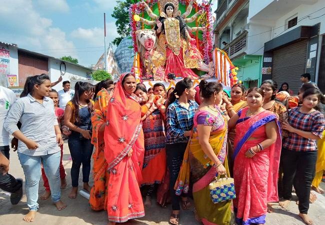 मां दुर्गा का विसर्जन करते लोग