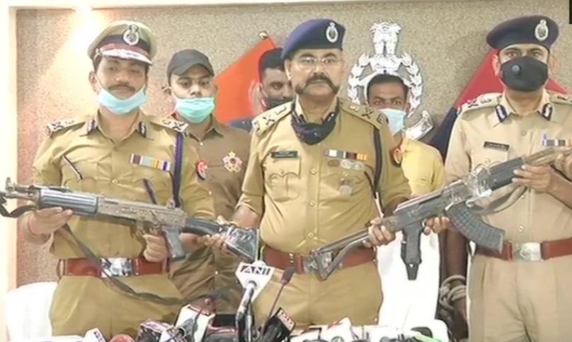 बरामद हथियारों के साथ प्रेस कांफ्रेंस में पुलिस अधिकारी