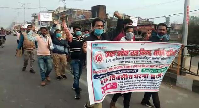 सड़क पर मार्च निकालते जल निगम कर्मचारी