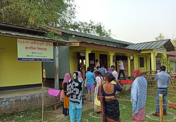 असम में मतदान के लिए खड़े लोग