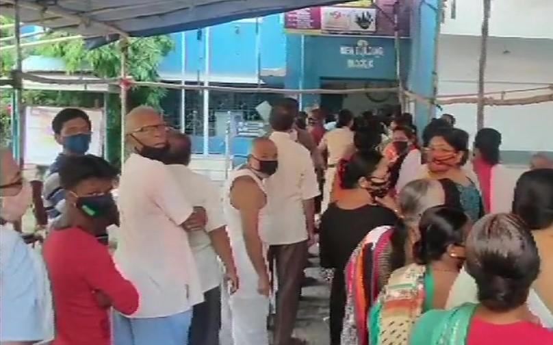 मतदान केंद्र पर वोटिंग के लिये अपनी बारी का इंतजार करते वोटर्स